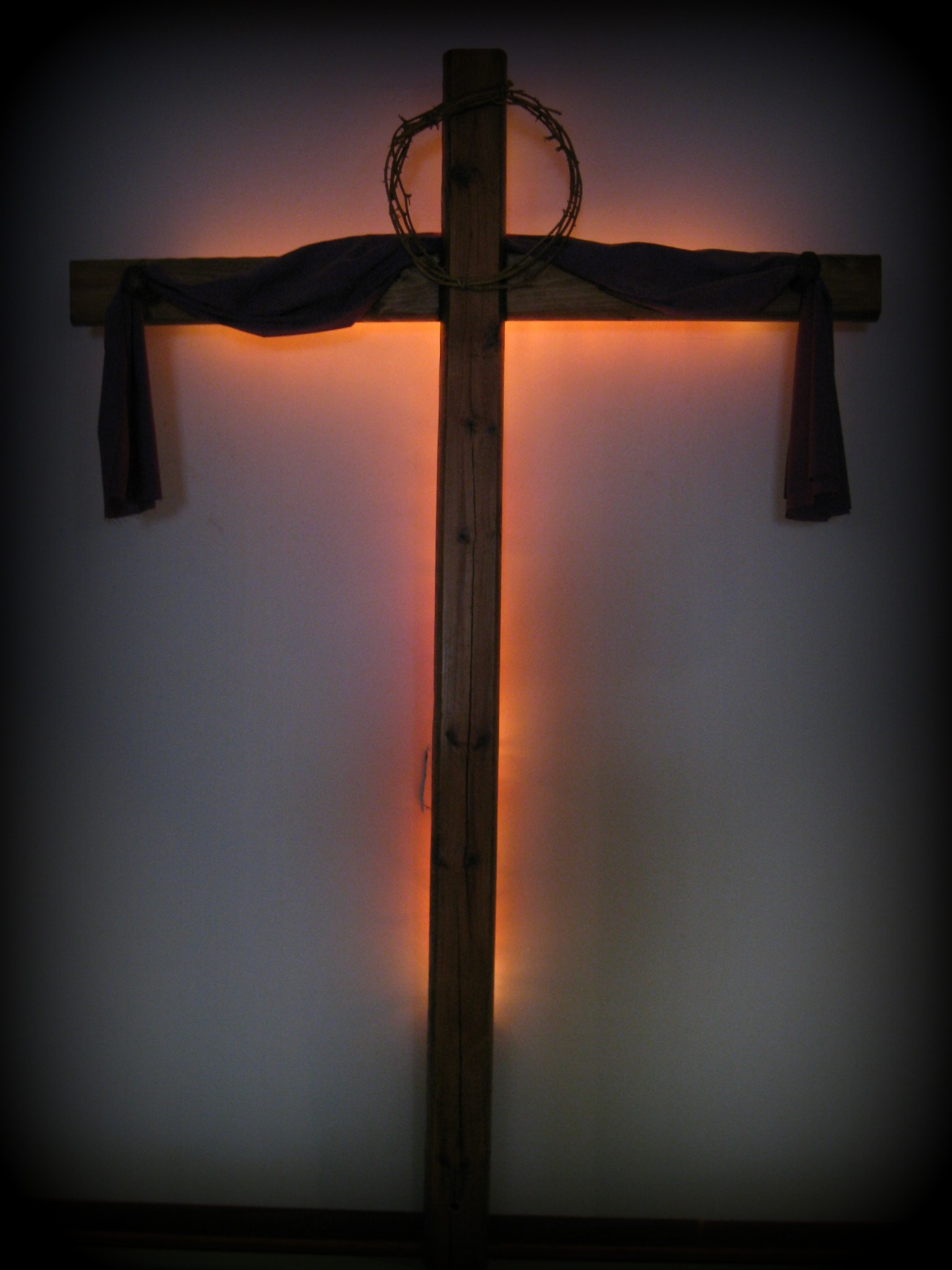 Cross behind our pulpit in the church building.